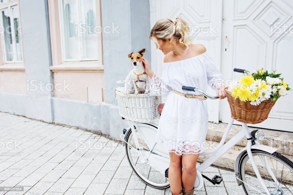 Beautiful, blond woman riding a bicycle in a town royalty-free stock photo