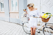 istock Beautiful, blond woman riding a bicycle in a town 905437554