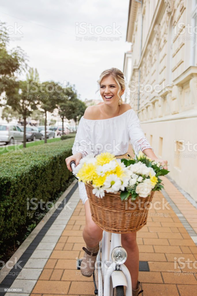 Beautiful, blond woman riding a bicycle in a town stock photo