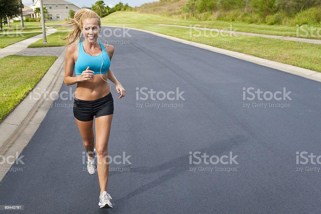 Schönen blonden Frau läuft und anhören MP3-Player Lizenzfreies stock-foto