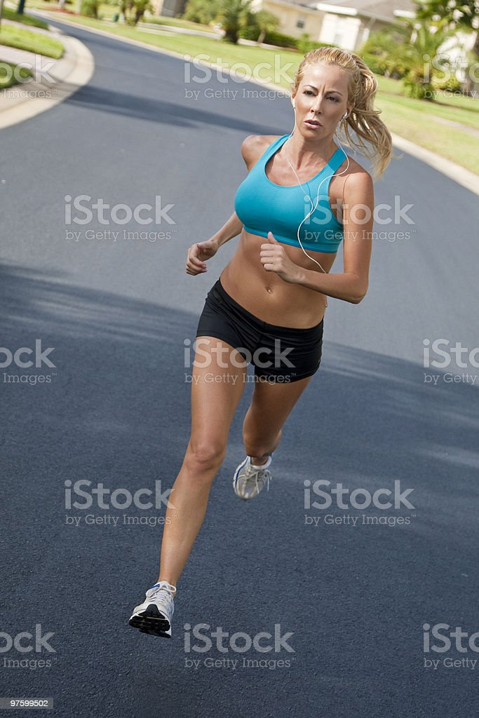 Beautiful Blond Woman Running and Listening to MP3 Player royalty-free stock photo