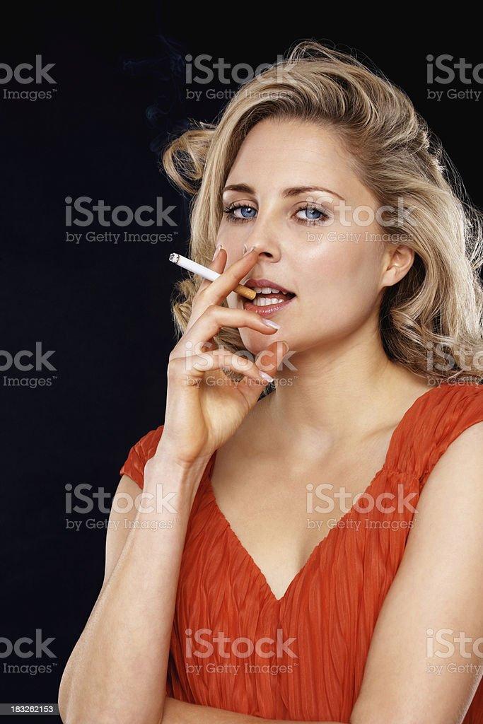 Beautiful blond woman smoking a cigarette royalty-free stock photo