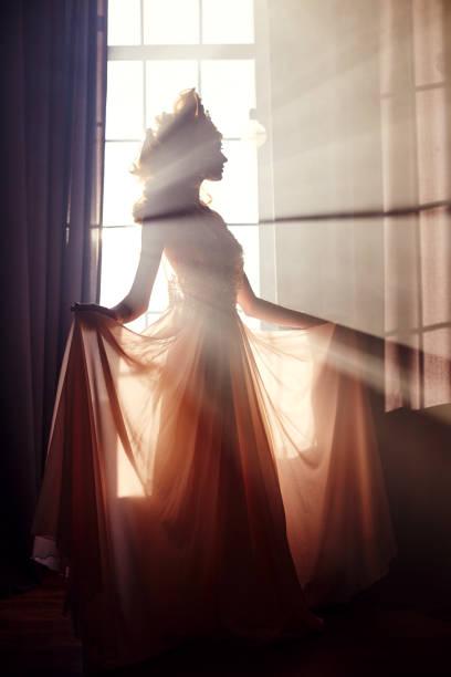 schöne blonde frau stehend in der sonne am fenster in einem lange beige kleid. fabelhafte märchen mit langen blonden haaren. kunst-mode-mädchen in den strahlen des lichtes auf dem hintergrund eines großen fensters - prinzessin tiara stock-fotos und bilder