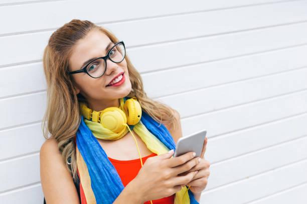 Beautiful blond woman using smart phone outdoors stock photo