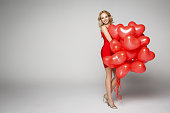 Beautiful smiling blond woman posing on grey background and holding balloons heart. Valentine's day.