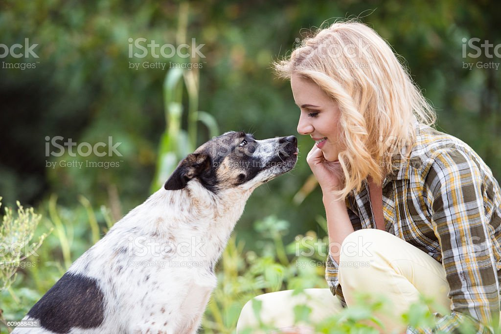 Beautiful blond woman with dog in green garden stock photo