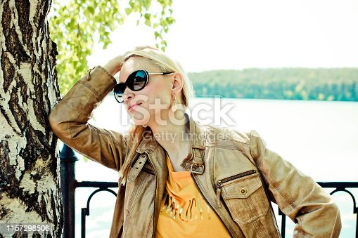 istock Beautiful blond woman with long hair in sunglasses posing near the tree. Natural light portrait. 1157298506