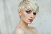 Beautiful blond woman with short hair and evening make-up looking at camera