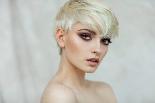 Beautiful blond woman with short hair and evening make-up looking at camera stock photo