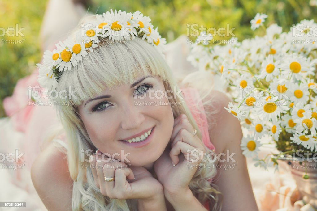 Beautiful blond young lady woman in pink airy dress happy smiling posing portrait on daisy meadow with basket bucket full of flowers chamomile and wreath anadem on top head. stock photo