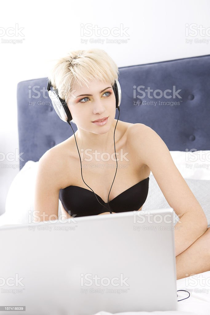 Beautiful Blond Young Woman Fashion Model, Using Laptop, Wearing Headphones royalty-free stock photo