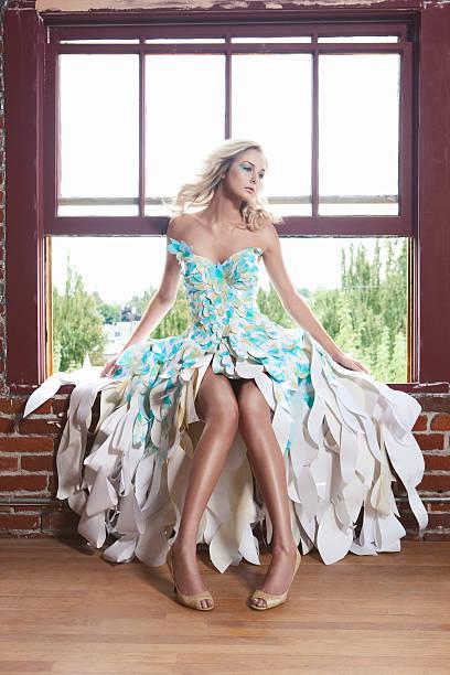wunderschöne blonde model in papier mode kleid auf fenster - abendkleid lang blau stock-fotos und bilder