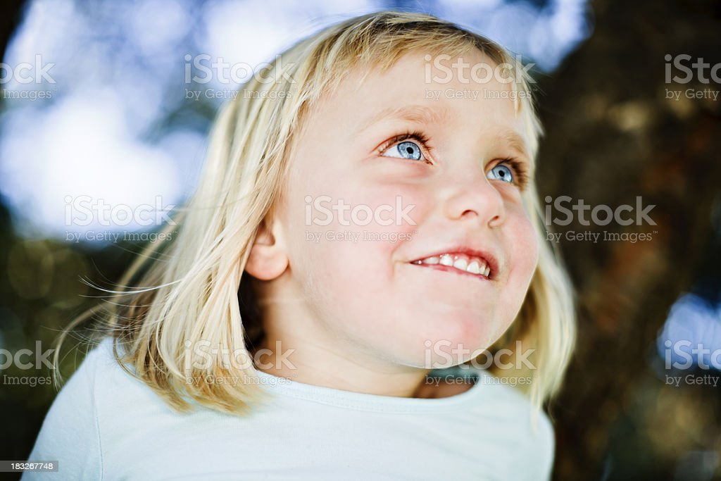 Beautiful blonde 3 year old smiles outdoors royalty-free stock photo