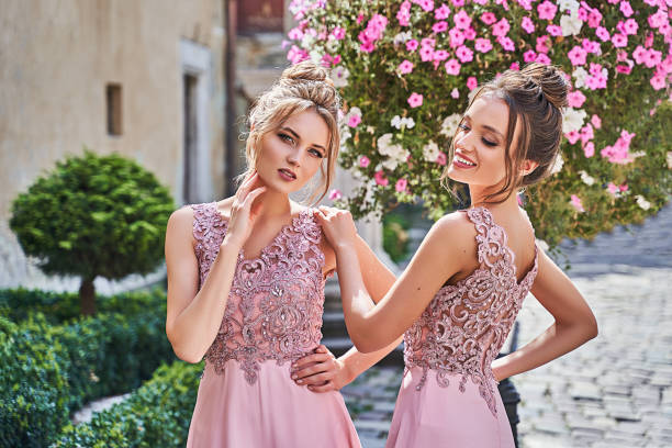 Beautiful blonde and brunette bridesmaids with luxury hairdo in gorgeous elegant stylish pale pink floor length v neck chiffon gown dress decorated with sequins sparkles and rhinestones on flowers background. Sunny summer wedding day in old beautiful Euro stock photo