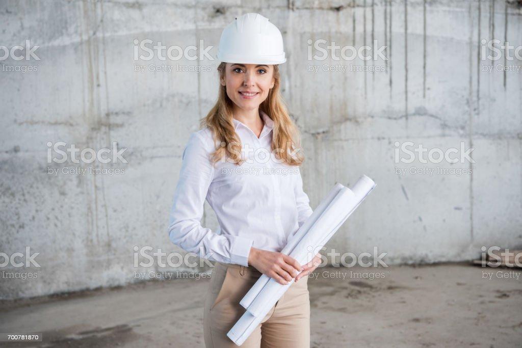 Schöne blonde Architekt im Helm holding Blaupausen und lächelt in die Kamera – Foto