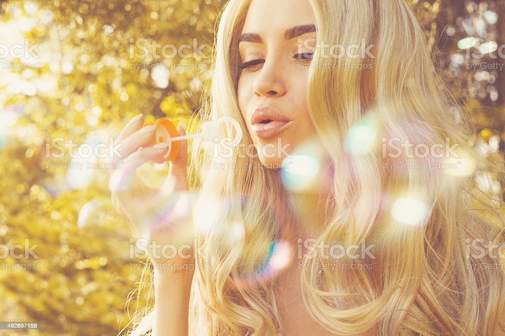 Beautiful blonde blowing bubbles stock photo