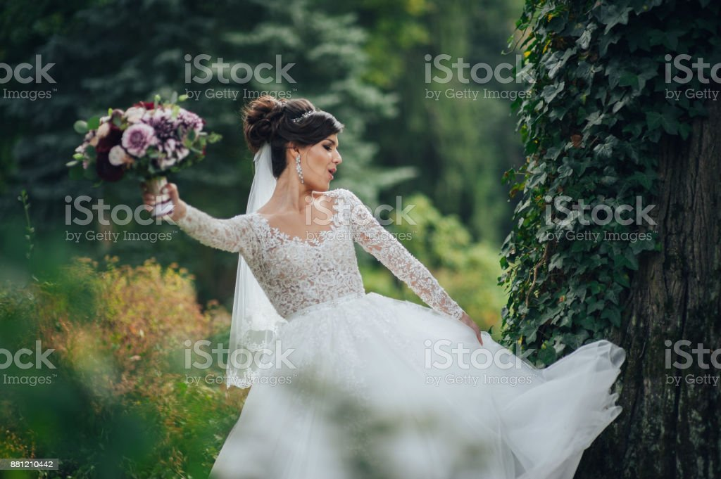 Beautiful blonde bride poses with orange wedding bouquet in the park stock photo