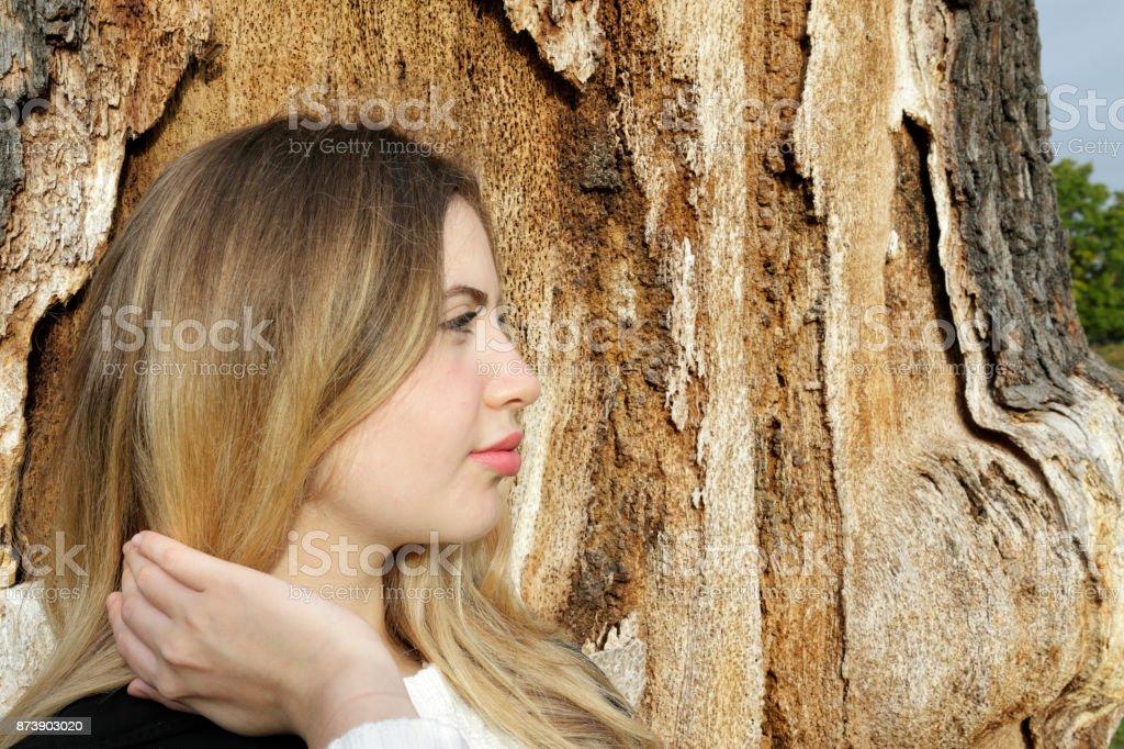 Beautiful blonde Bulgarian outdoor girl profile character tree trunk stock photo