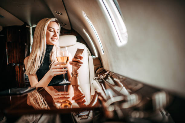 Beautiful blonde businesswoman drinking wine and using a smart phone on a private airplane stock photo