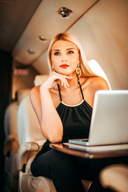 Beautiful blonde businesswoman pondering while working on the go using a laptop while traveling on a private jet stock photo