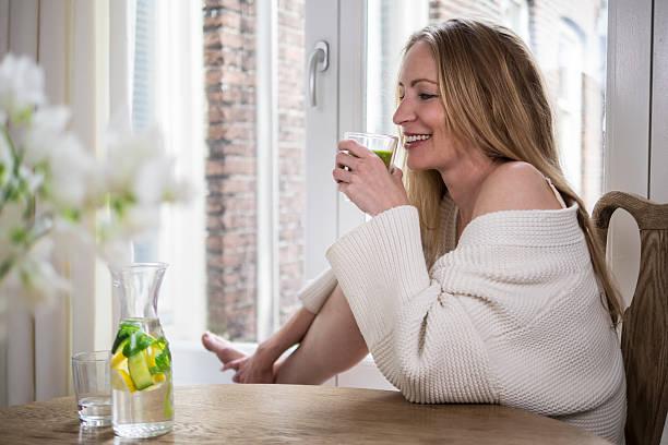 Wunderschöne blond trinkt einen grünen smoothie am Morgen – Foto