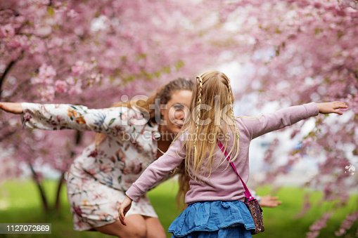 Beautiful blonde dutch mother and child daughter together in a Cherry Blossom Forest