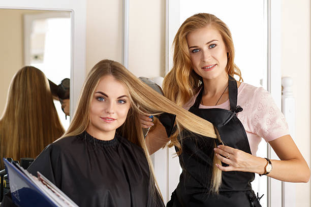 Beautiful blonde female hairdresser holding scissors, comb and h stock photo