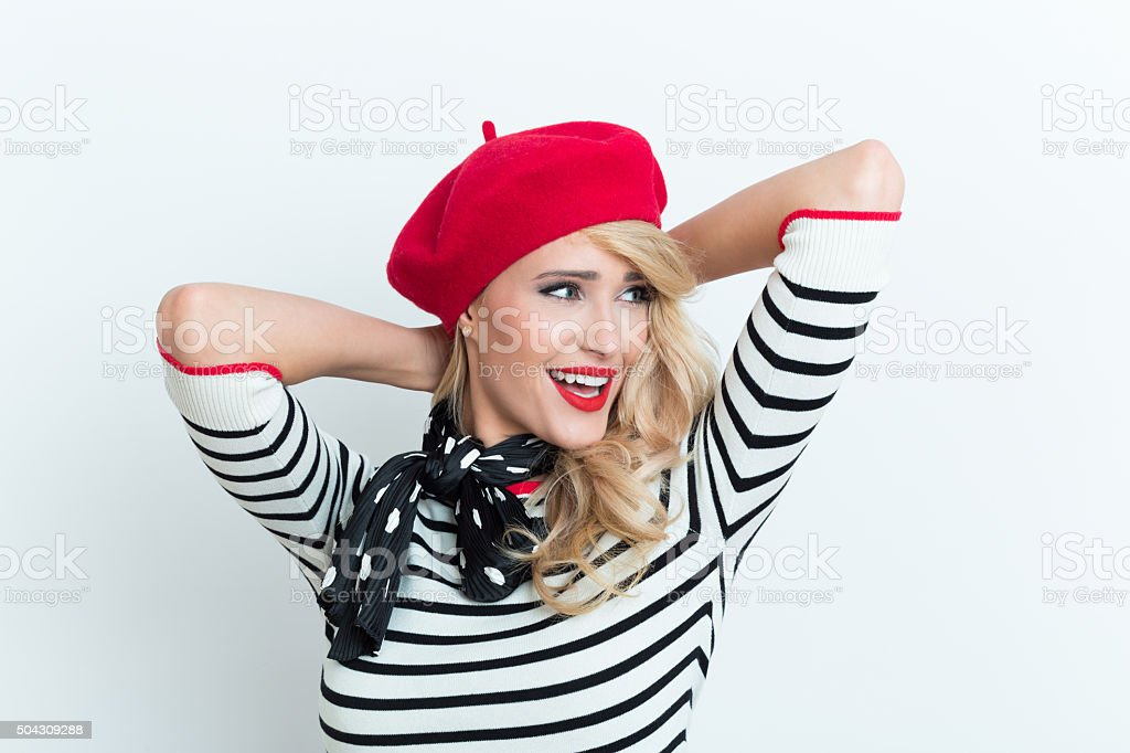 Beautiful blonde french woman wearing red beret Portrait of beautiful blonde woman in french outfit, wearing a red beret, striped blouse and neckerchief, standing with raised arms. Adult Stock Photo