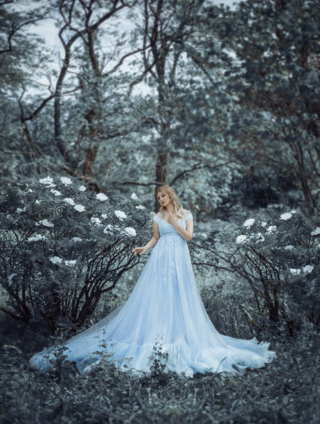 美しいブロンドの女の子、モデルサイズプラス、植物の中を歩く、先駆的な牡丹を背景に庭を咲かせる。女の子は、王女のような豪華な、緑豊かな青いドレスを持っています。アートフォト - プリンセス ストックフォトと画像