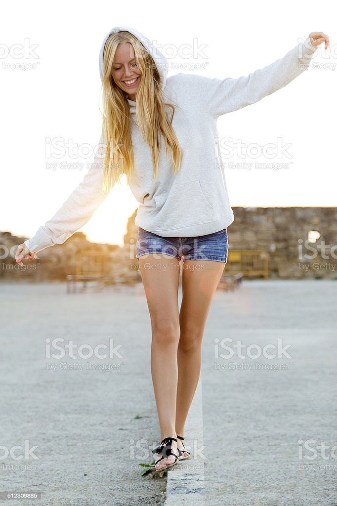 Beautiful blonde girl balancing on a curb in the city. stock photo