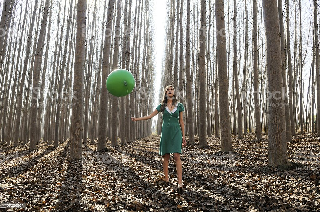 Beautiful blonde girl, dressed in green, walking into the forest royalty-free stock photo