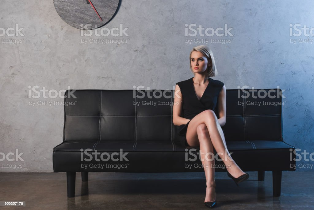 beautiful blonde girl in black dress and high heeled shoes sitting on couch and looking away stock photo