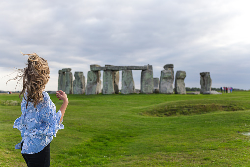 Beautiful girl with windy hair standing and looking at Stonehenge.