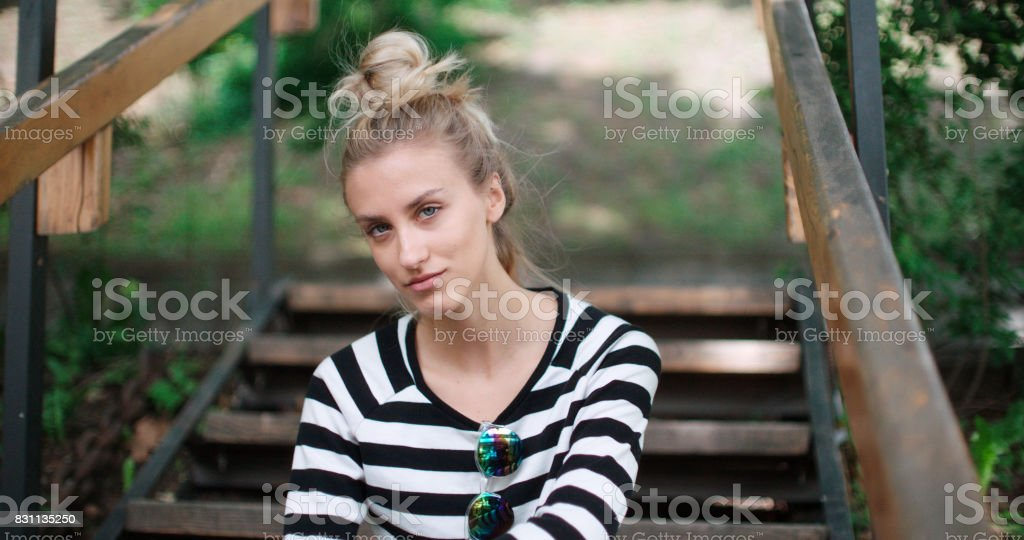 Beautiful blonde girl looking to a camera and smiling. stock photo