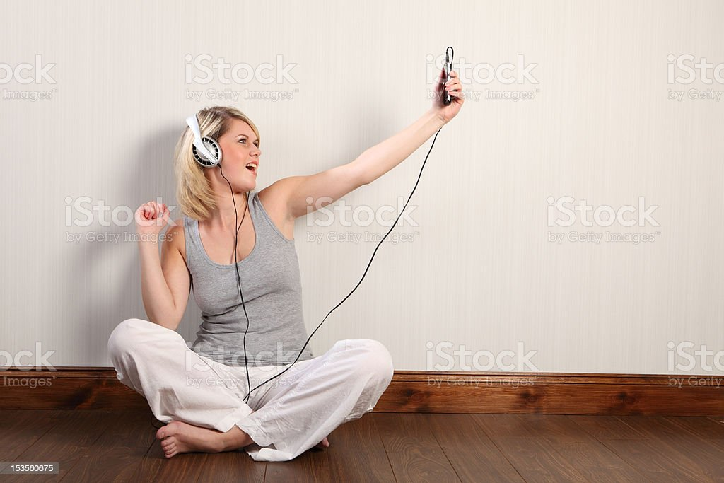 Beautiful blonde girl singing to music at home royalty-free stock photo