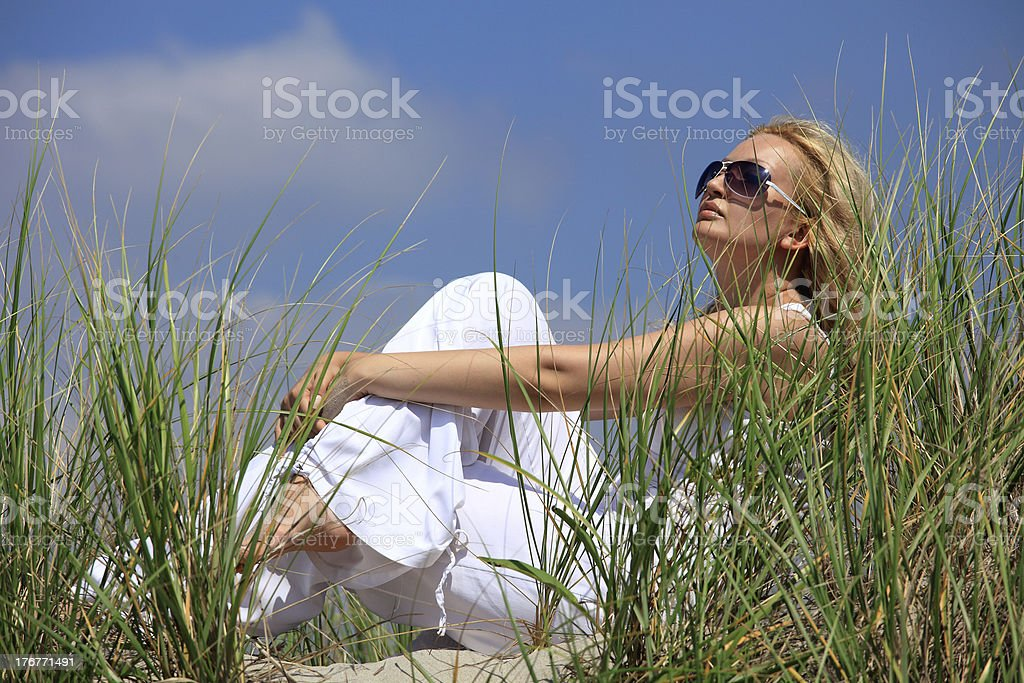 Beautiful blonde girl sitting on a sand in dunes royalty-free stock photo