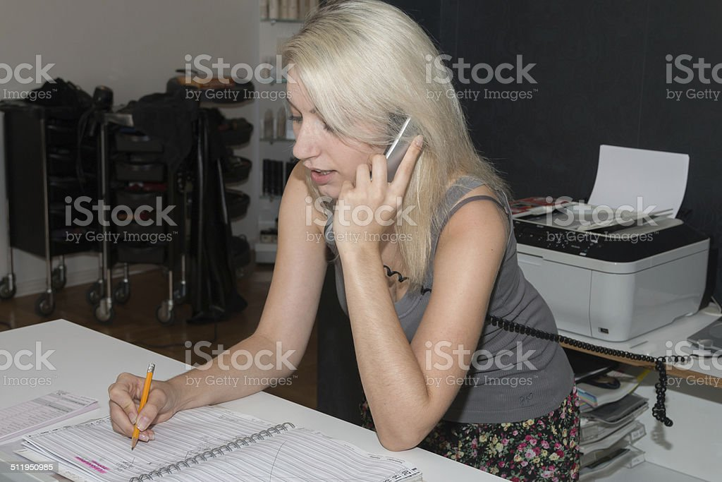 Beautiful blonde girl taking a phone call stock photo