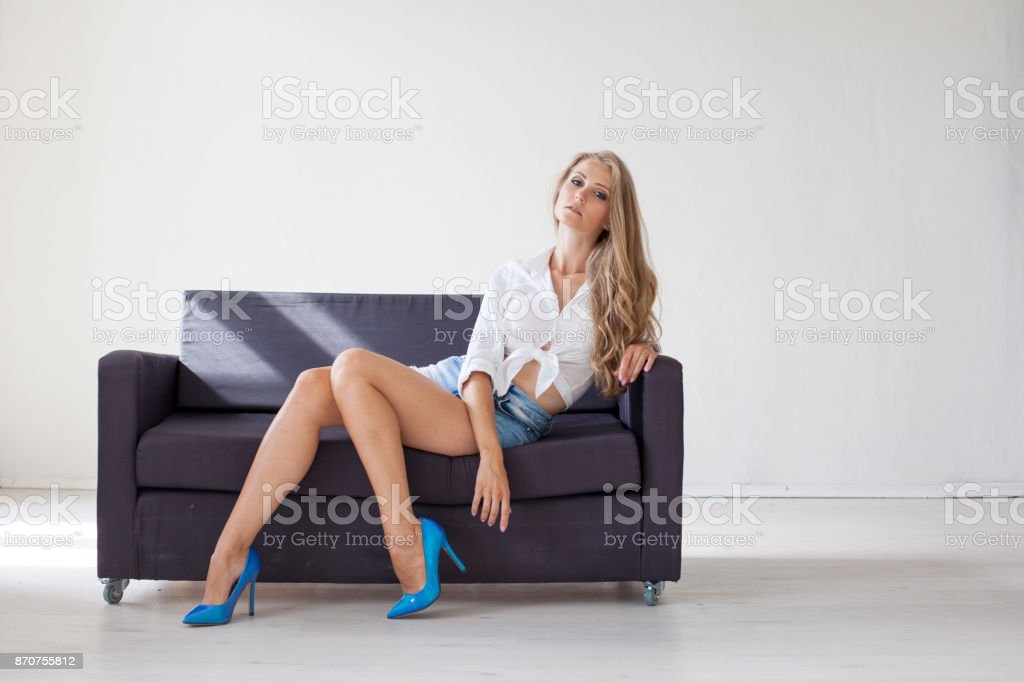 beautiful blonde girl with blue eyes sitting on the couch in a white room 1 stock photo