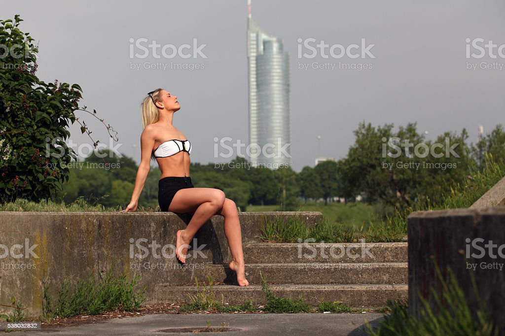 Beautiful blonde girl with hot pants and bikini sunbathing stock photo