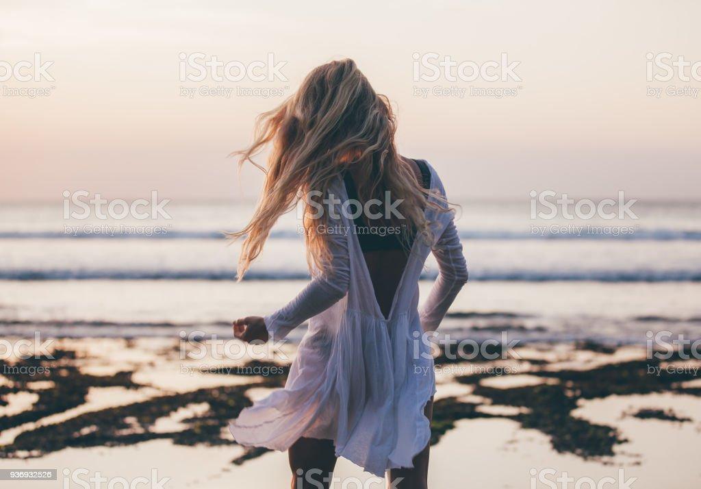 3d59271ebf47 Vacker blond tjej med långt hår kort vit klänning dans vid solnedgången  royaltyfri bildbanksbilder