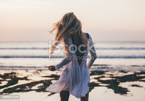 istock Beautiful blonde girl with long hair in short white dress dancing at sunset 936932526