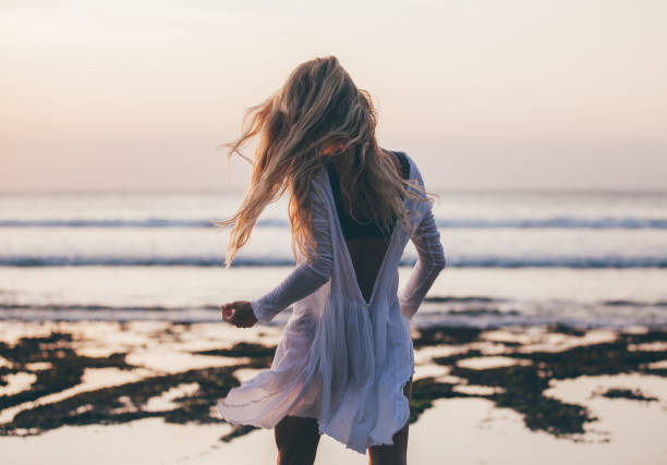 Beautiful blonde girl with long hair in short white dress dancing at sunset stock photo