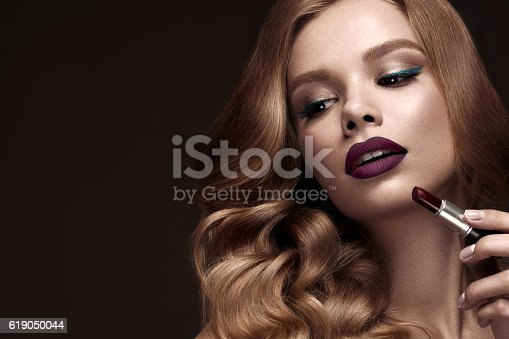 istock Beautiful blonde in a Hollywood manner with curls, dark lips 619050044