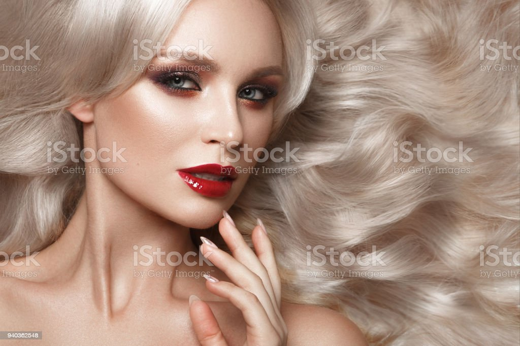Beautiful blonde in a Hollywood manner with curls, natural makeup and red lips. Beauty face and hair. - Stock image .