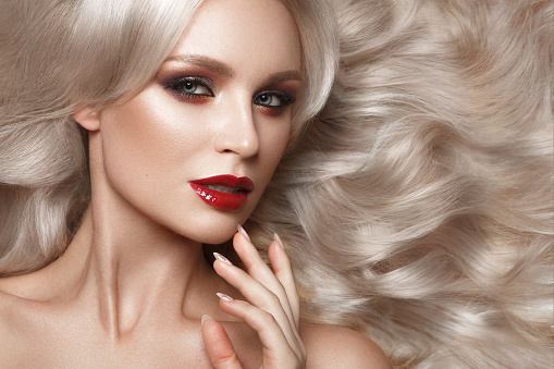 istock Beautiful blonde in a Hollywood manner with curls, natural makeup and red lips. Beauty face and hair. 940362548