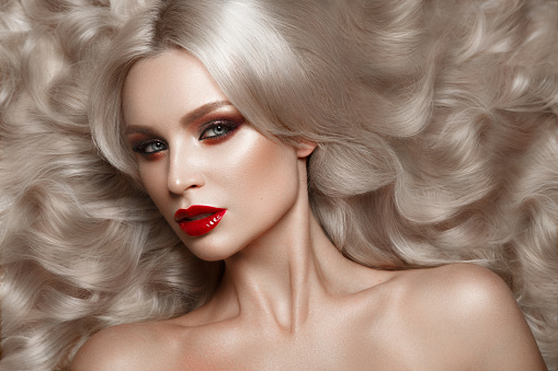 istock Beautiful blonde in a Hollywood manner with curls, natural makeup and red lips. Beauty face and hair. 940362550