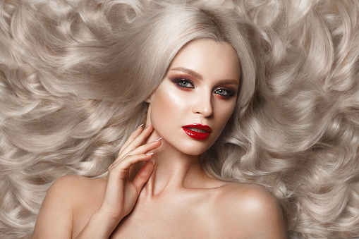 istock Beautiful blonde in a Hollywood manner with curls, natural makeup and red lips. Beauty face and hair. 940362560