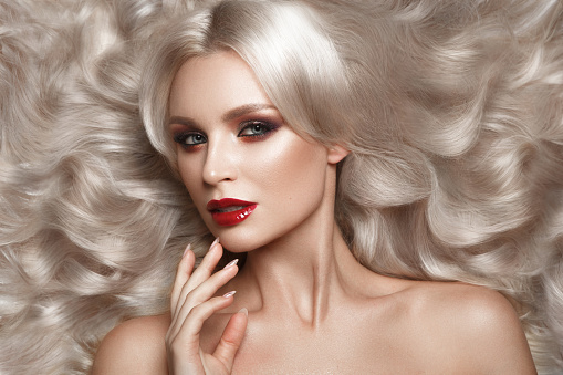 istock Beautiful blonde in a Hollywood manner with curls, natural makeup and red lips. Beauty face and hair. 940362566