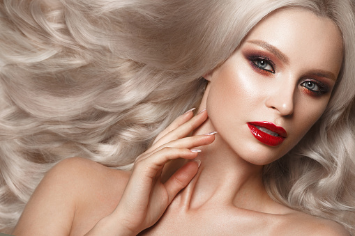 istock Beautiful blonde in a Hollywood manner with curls, natural makeup and red lips. Beauty face and hair. 940362574