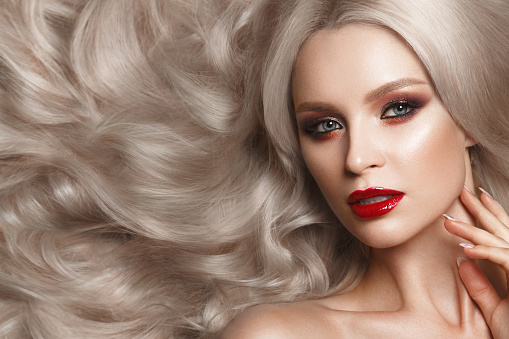 istock Beautiful blonde in a Hollywood manner with curls, natural makeup and red lips. Beauty face and hair. 940362576